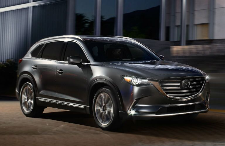 2018 Mazda CX-9 driving by a building