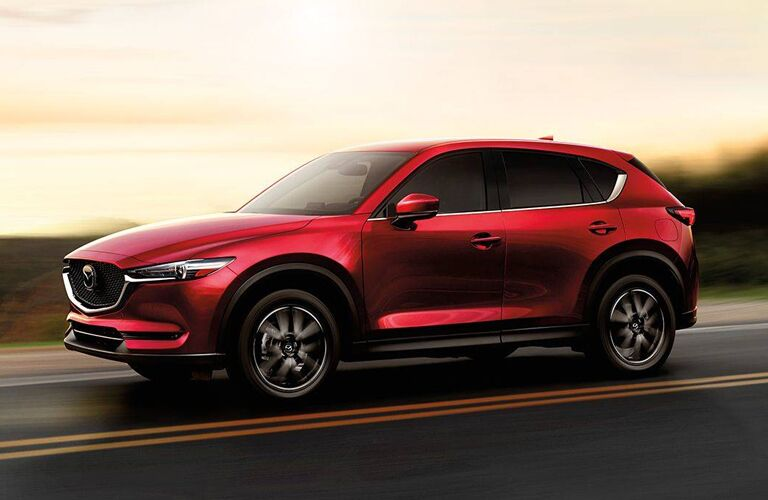 2018 Mazda CX-5 driving on a road with the sun setting in the background