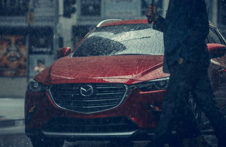 2019 Mazda CX-3 in the rain with a man walking by