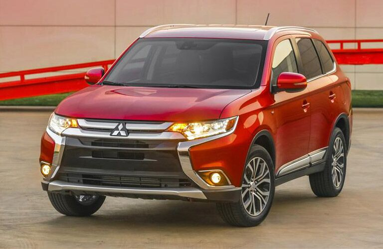 2016 Mitsubishi Outlander exterior front fascia and drivers side in front of tiled building