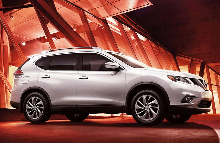 2016 Nissan Rogue exterior passenger side profile with red lighting background