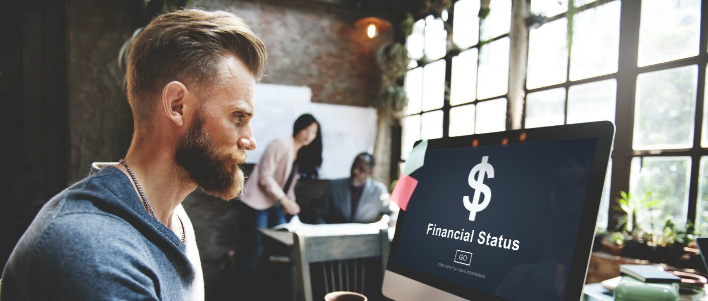 """Man looking at computer screen with """"Financial Status"""" on screen"""