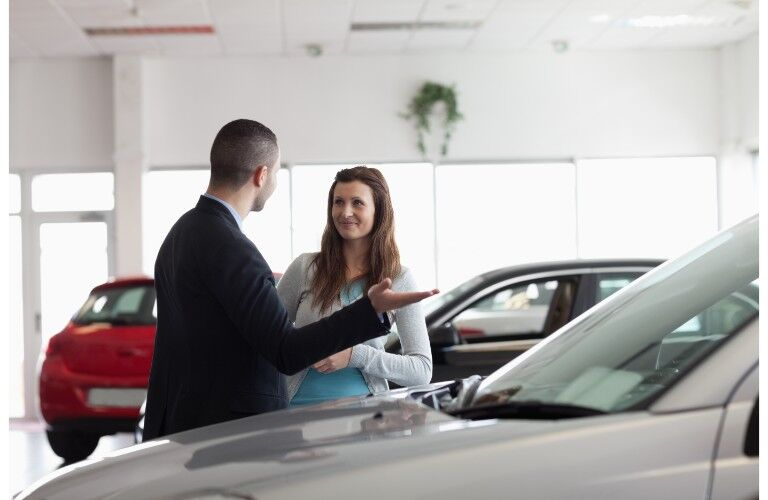 Car salesman talking to woman by car