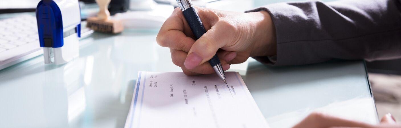 Closeup of hand signing a check