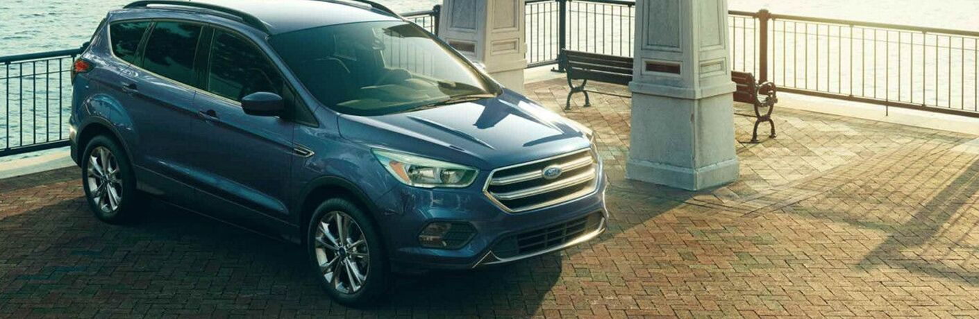 Blue 2018 Ford Escape Sitting ona patio in front of a fence near the water.
