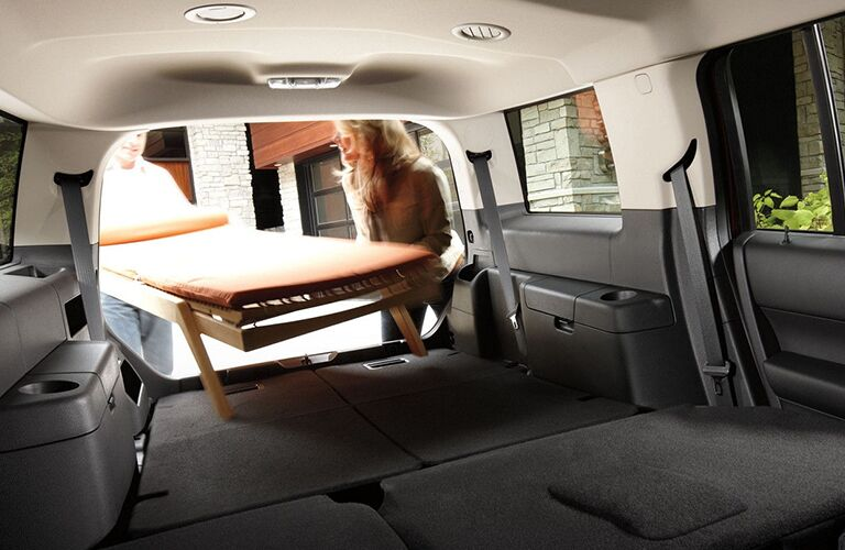 A couple putting a bed inside of a 2018 Ford Flex