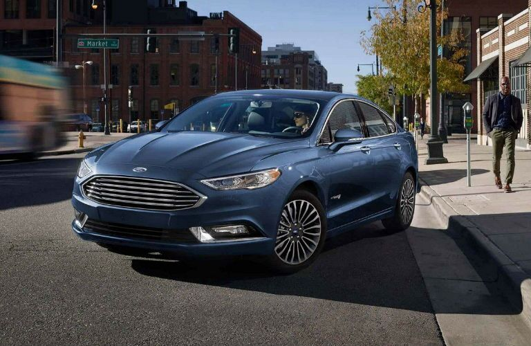 Blue 2018 Ford Fusion pulling away from the sidewalk