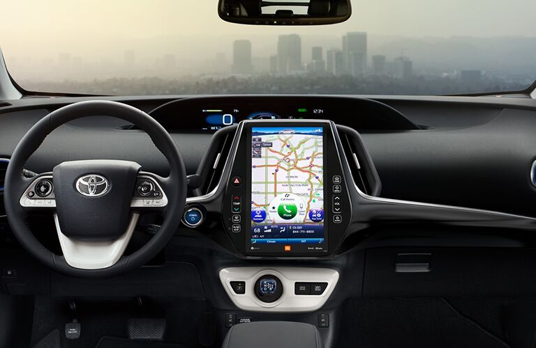 The display screen of the infotianment system is emphasized in the center of the dashboard of a Toyota Prius.