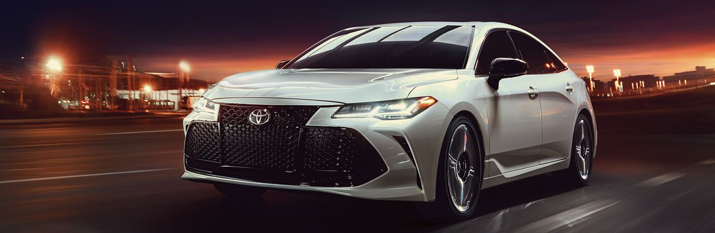 2019 Toyota Avalon Hybrid driving in a city at night