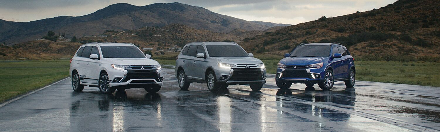 Three Mitsubishi SUVs parked in the rain