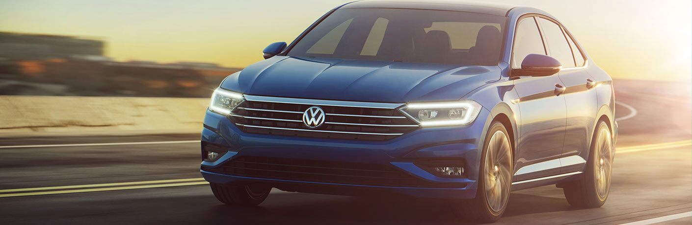 blue Volkswagen Jetta driving on a country highway