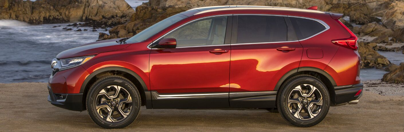 2019 Honda CR-V exterior side shot with molten lava pearl paint color parked on a sandy beach near ocean waves and rocks in the water