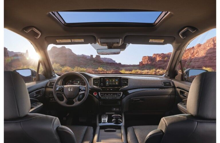 2019 Honda Passport interior shot of front seating, steering wheel, dashboard layout, moon roof, and view through windshield of rocky red cliffs