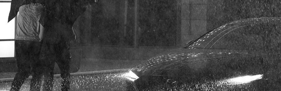 Two people running through heavy rain to running 2019 Mazda3
