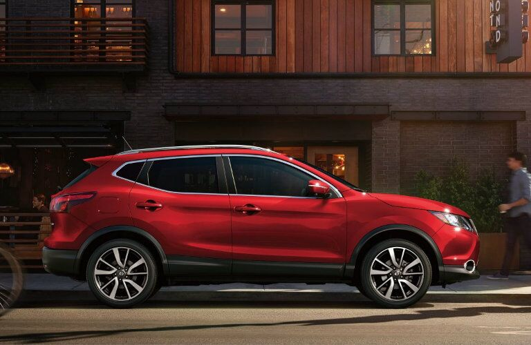 2018 Nissan Rogue Sport parked by a building with people walking by