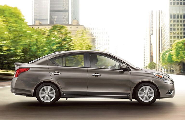 2018 Nissan Versa Sedan profile view with a city backdrop