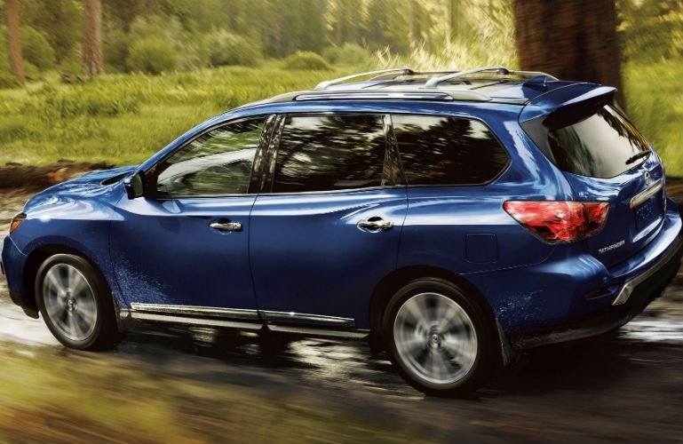 2019 Nissan Pathfinder Platinum 4WD in Caspian Blue Metallic driving through a woods