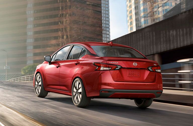 Rear view of red 2020 Nissan Versa on city road
