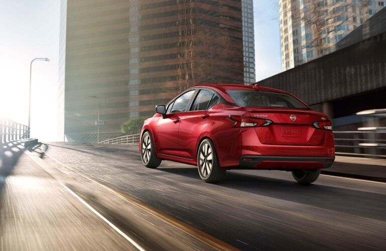 Rear driver angle of a red 2020 Nissan Versa sedan driving down a road