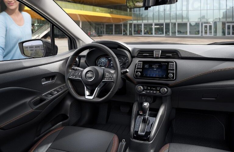 Front driver interior in the 2020 Nissan Versa sedan with a smiling woman outside the driver door