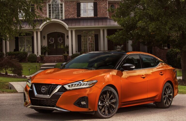 2020 Nissan Maxima in front of large brick house