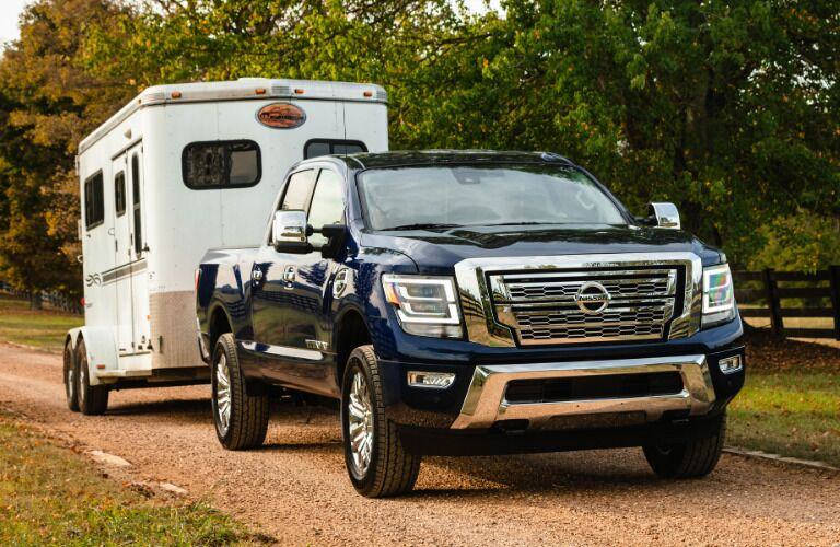 Front view of dark blue 2020 Nissan TITAN XD SL towing a trailer