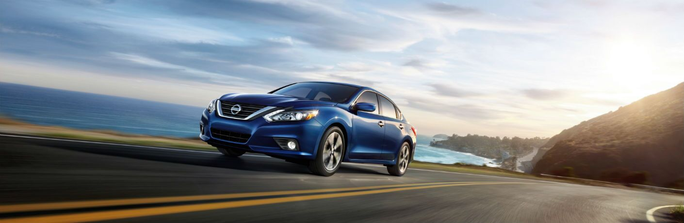 blue 2018 nissan altima driving on road near ocean