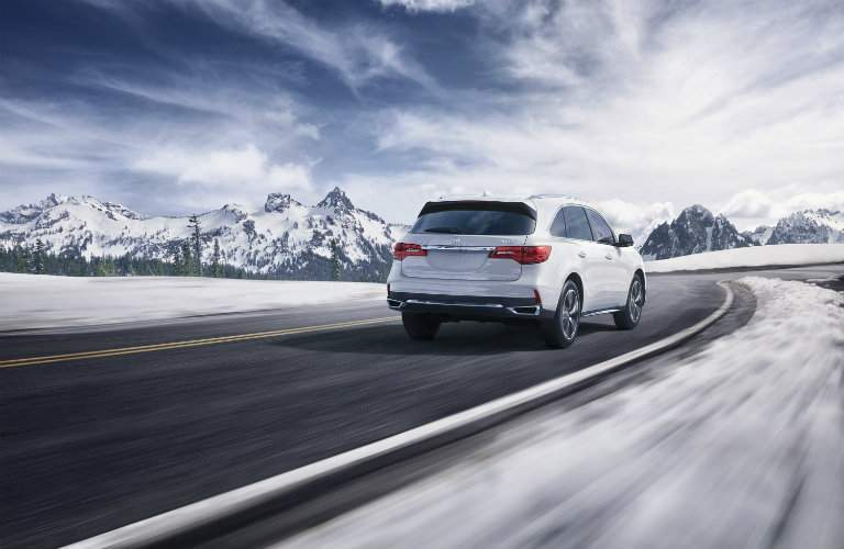 rear view of white 2018 Acura MDX driving through snowy mountains