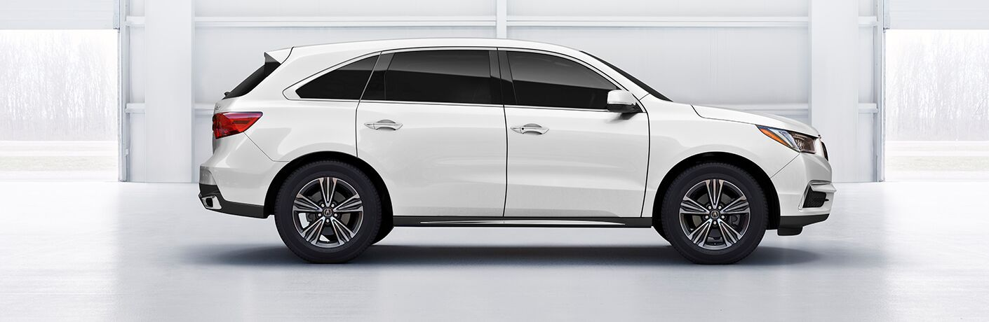 white 2019 Acura MDX in a white room side view