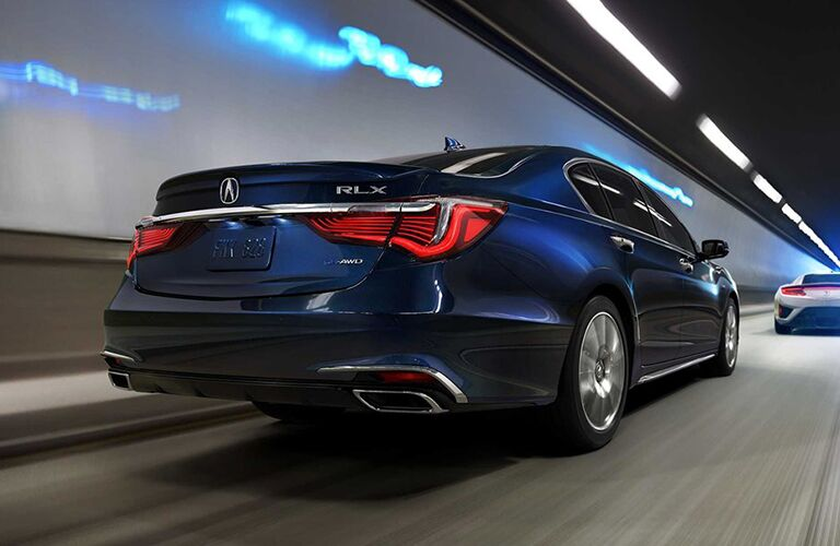 Rear shot of blue 2019 Acura RLX driving through tunnel