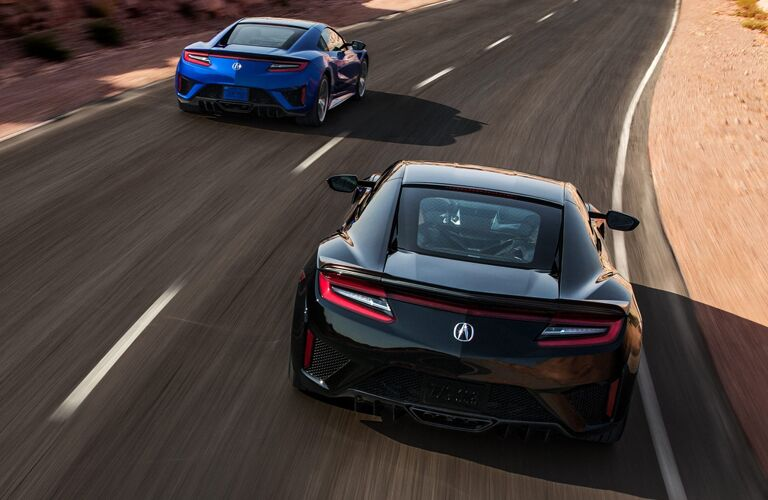 Rear view of blue 2020 Acura NSX and black 2020 Acura NSX