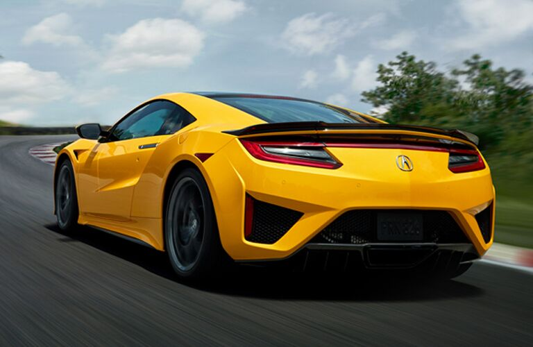 Driver's side rear angle view of yellow 2020 Acura NSX