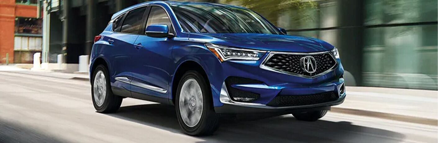Blue 2021 Acura RDX driving on a city street