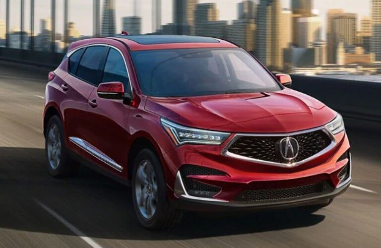 Red 2021 Acura RDX driving across a bridge