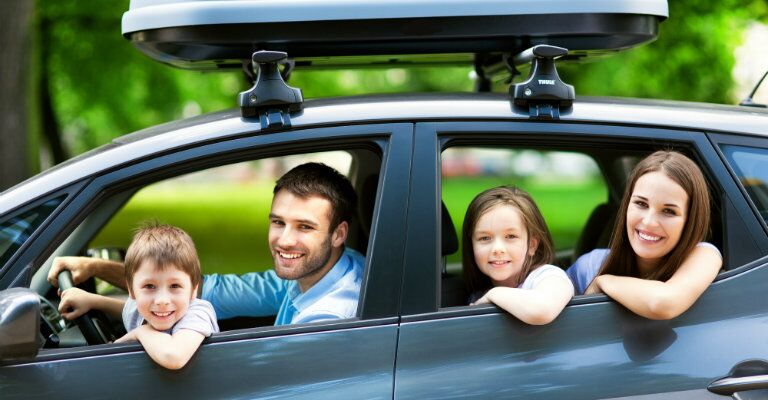 family of four looking out windows of an SUV