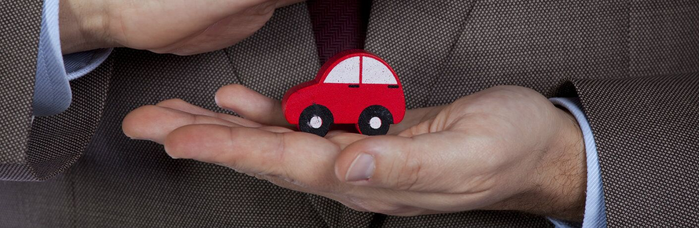 man_in_suit_holding_red_toy_car_in_hand