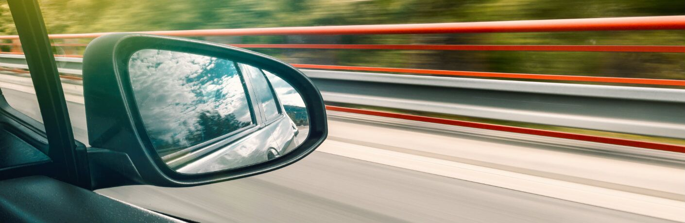 view_of_vehicle_side_mirror_out_of_passenger_window_of_moving_car