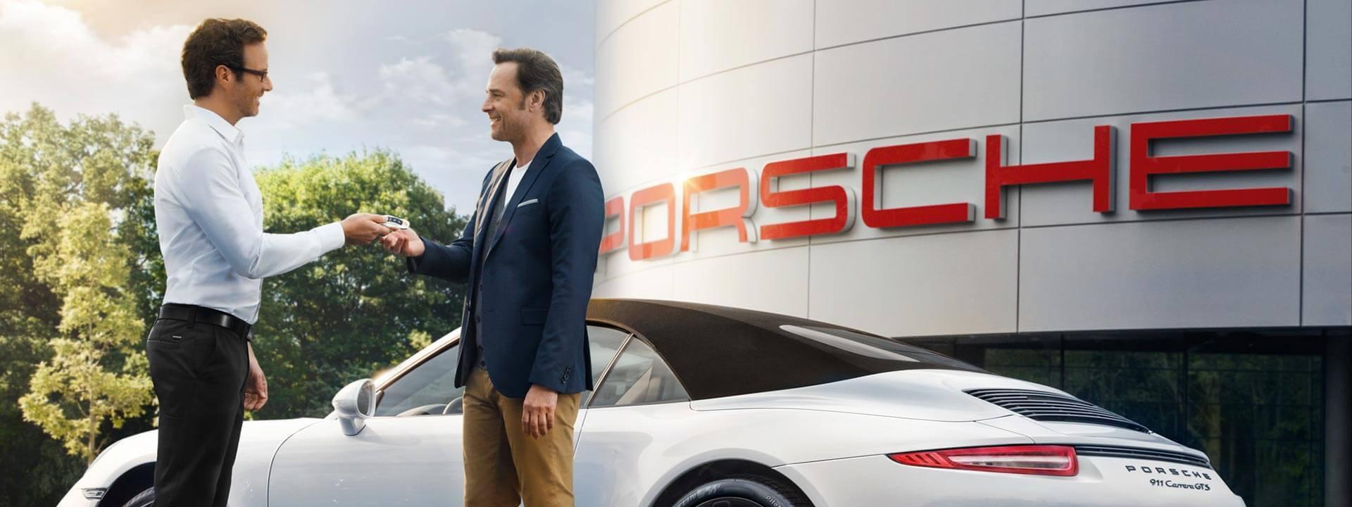 Two men exchanging Porsche keys in Bakersfield