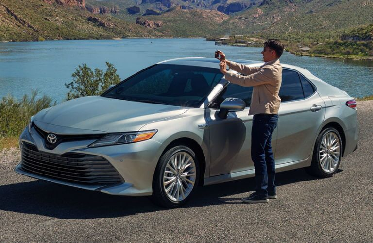 2018 Toyota Camry Hybrid Exterior Front Fascia and Drivers Side with Man Taking Photo Near Lake