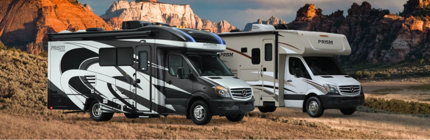 Exterior view of two 2018 Coachmen Prism 2150 Class C Motorhomes placed against a mountain background