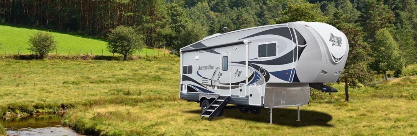 Exterior view of a 2019 Northwood Arctic Fox 27-5L parked in a campground