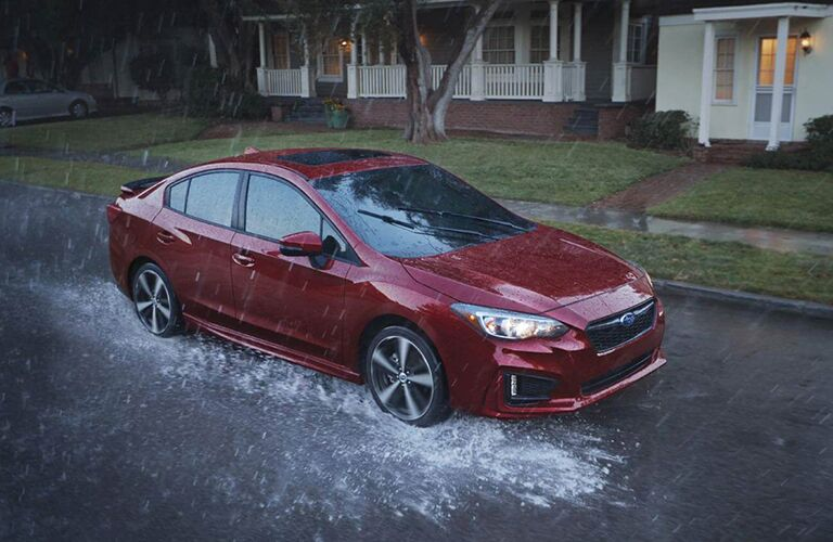 2019 Subaru Impreza driving down a flooded street in rain