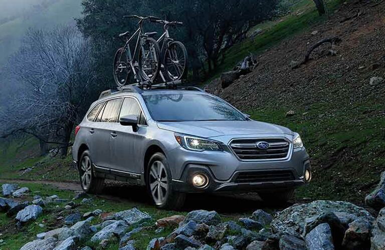 2019 Subaru Outback driving down a dirt road with two bikes attached on top