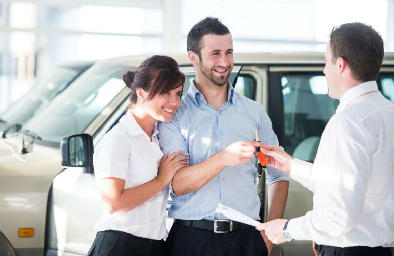 A stock photo of people handing their keys to a dealership representative.