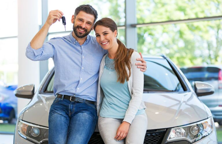 A stock photo of a couple hold up the keys of a vehicle they just purchased.