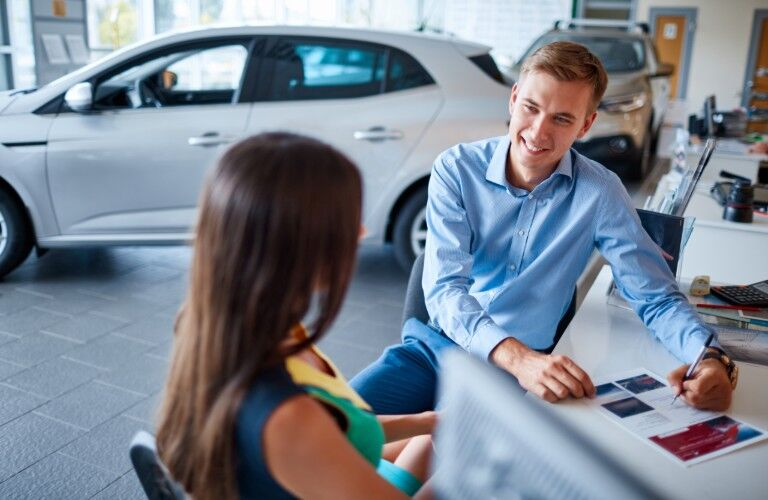A salesman and a woman talk about business at a table in a car dealership