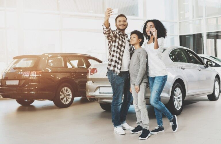 An African American family holding car keys and taking picture with a smartphone in a car dealership