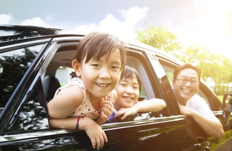 A girl, boy and their dad are pictured with big smiles, hanging out the window of a car