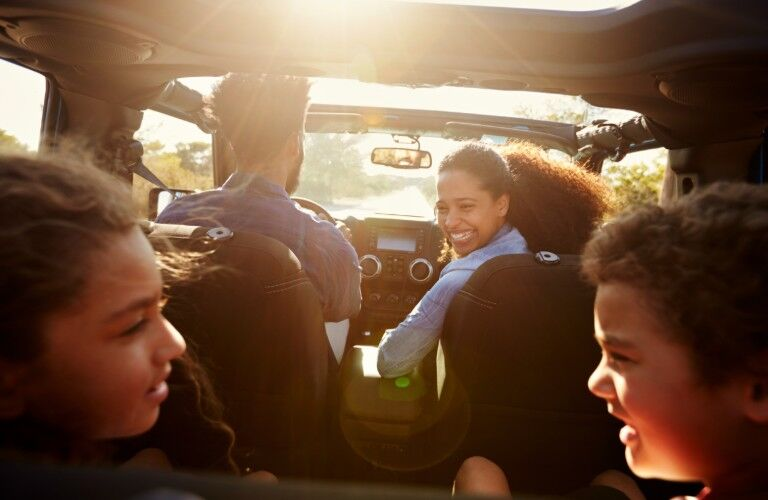 An African American mother seated in the passenger's seat, is smiling at the children in the backseat while her husband drivers the SUV