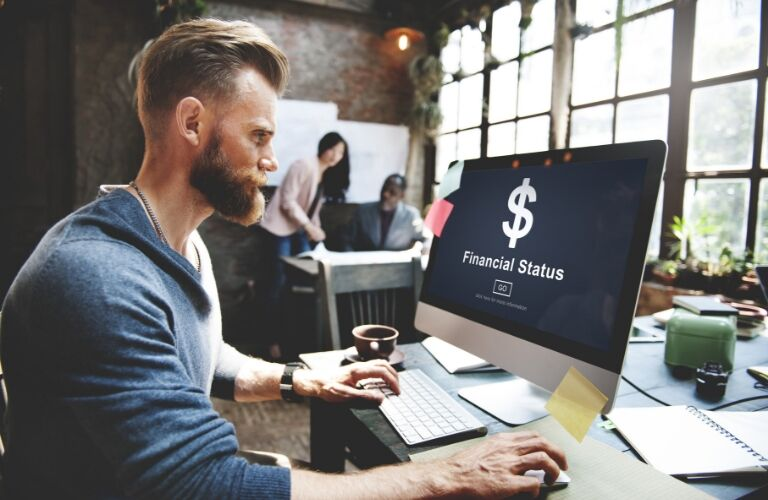 """Man sitting at computer with """"financial status"""" on the screen"""